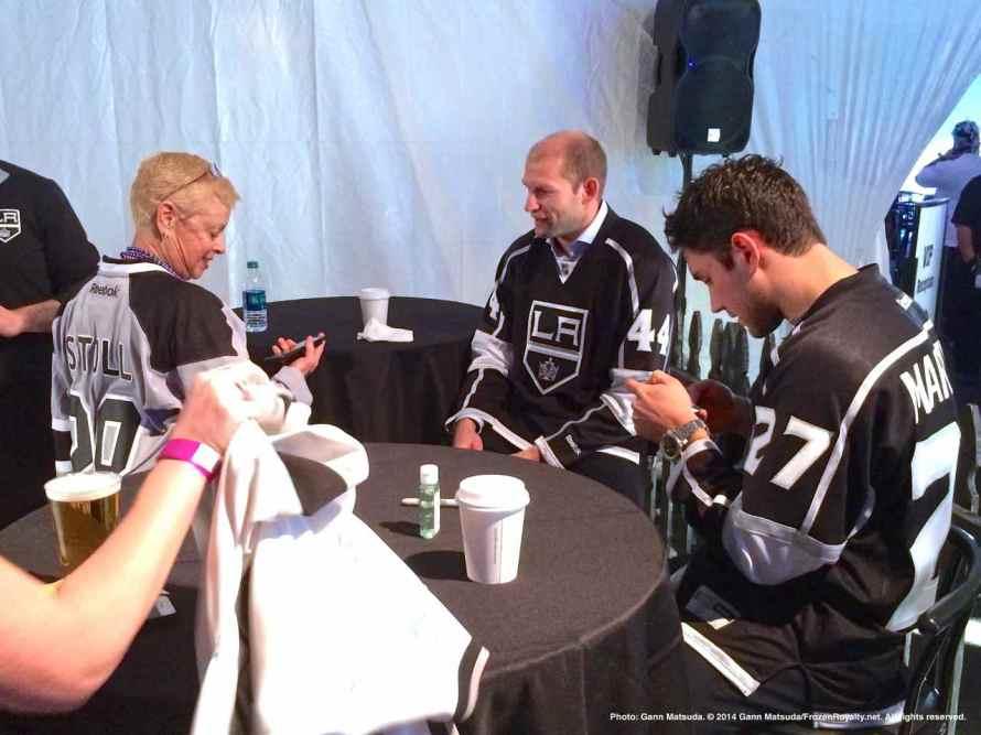 Defensemen Robyn Regehr (center) and Alec Martinez (right) greet a fan