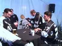 Defensemen Robyn Regehr (center) and Alec Martinez (right) sign autographs