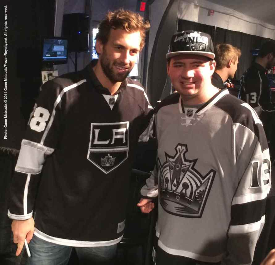 Cetner Jarret Stollposes for a photograph with a fan