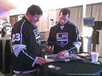 Left Wing Kyle Clifford autographs the Kings' 2012 Stanley Cup Championshp commemorate book for a fan