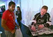 Defenseman Matt Greene signs an autograph for a fan