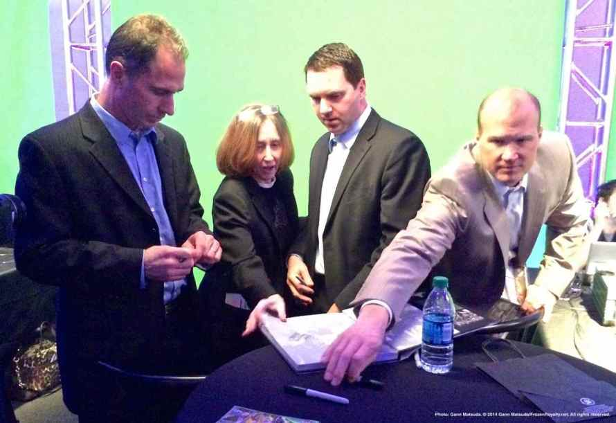 Assistant coaches John Stevens (left), goaltender coach Bill Ranford (second from right), and assistant coach Davis Payne (right) sign autographs for a fan