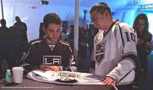 Defenseman Alec Martinez signs a jersey for a fan