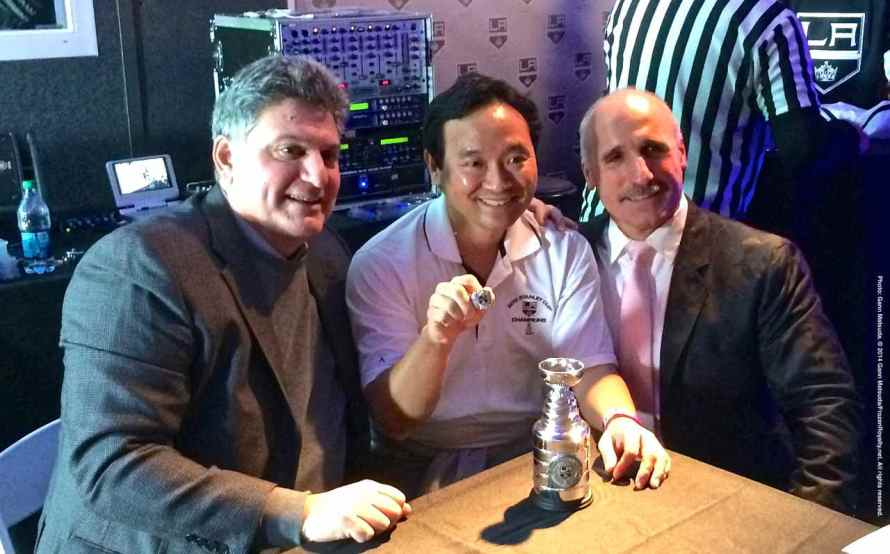 Radio play-by-play announcer Nick Nickson (left) and radio color commentator Daryl Evans (right) with a fan