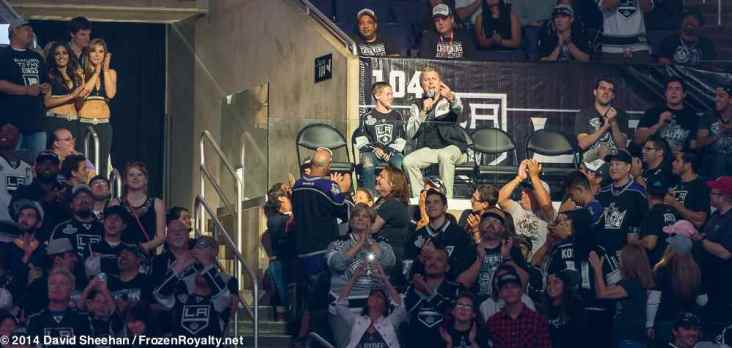LA Kings in-arena cost Jay Flats (spotlighted, with microphone in hand) with a young fan.