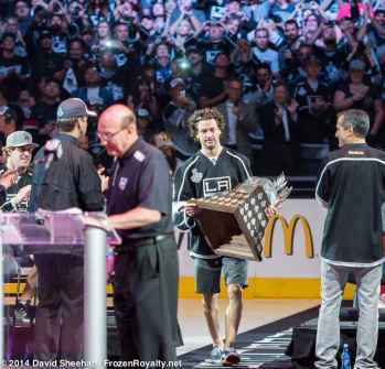Right wing Justin Williams carries the Conn Smythe Trophy onto the ice.