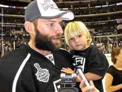 Defenseman Robyn Regehr (and his son) speaks to the media.