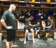 LA Kings forward Jeff Carter signs nine-year-old cancer patient Grace Bowen's jersey, while winger Marian Gaborik (left) and right wing Justin Williams (right) look on.