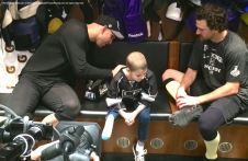 LA Kings left wing Dwight King signs nine-year-old cancer patient Grace Bowen's jersey, while right wing Justin Williams observes.